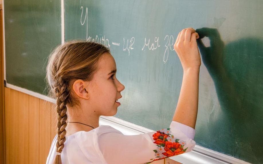Дівчинка на дошці пише слово Україна