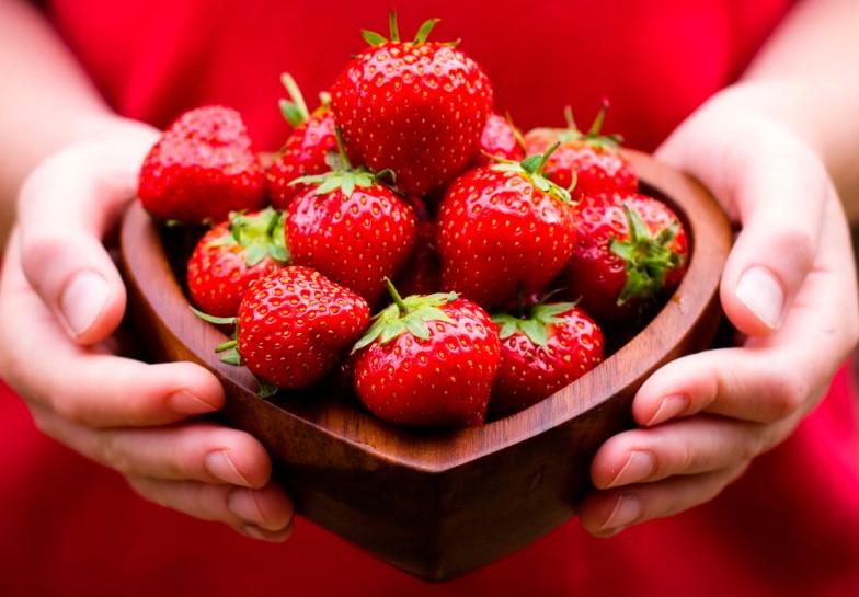 Врожай полуниці в руках у жінки