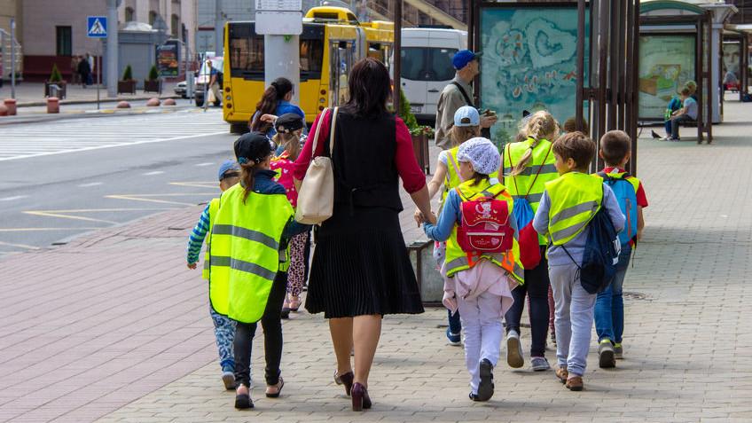 Вчителька зі школярами в світловідбиваючих жилетах