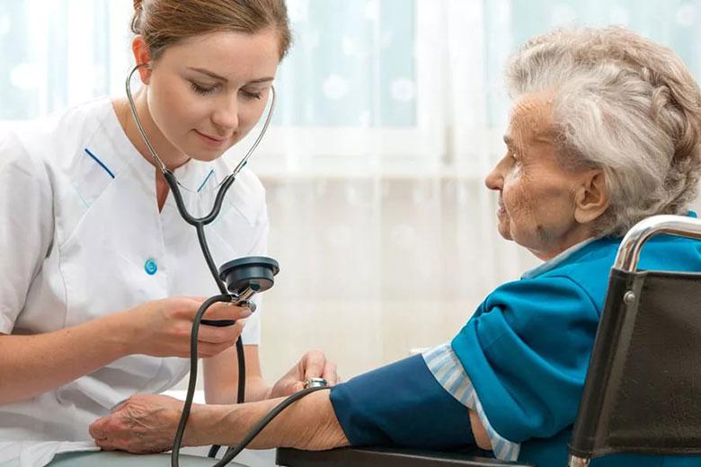 Медсестра доглядає за хворою бабусею